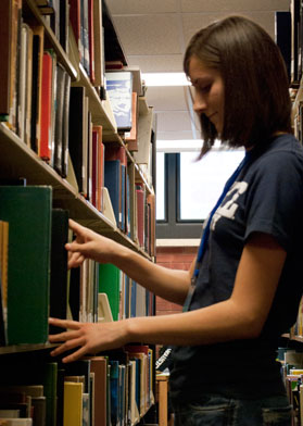 Cowles Library student assistant reshelving a book